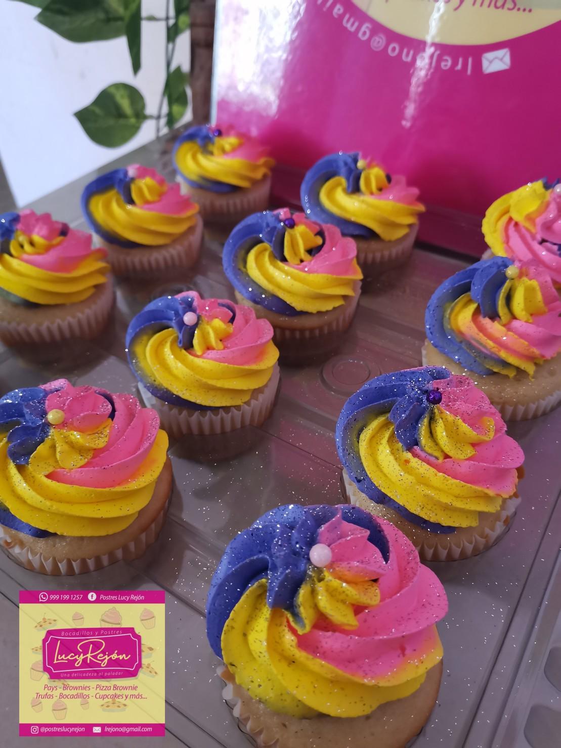 Cupcakes de vainilla o chocolate con crema batida en 3 colores amarillo, rosado y morado con sprinkles y diamantina comestible